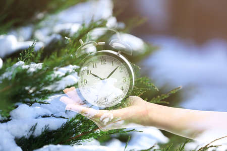 Time change concept. Double exposure of female hand holding alarm clock and branches covered with snow