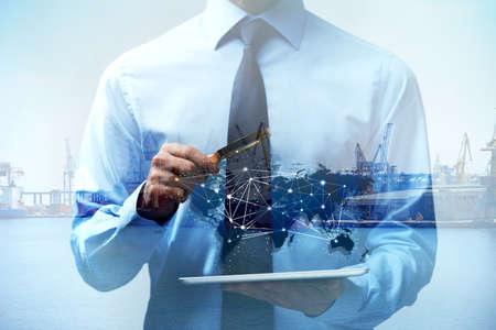 Double exposure of seaport and man holding tablet with magnifier. Logistic concept