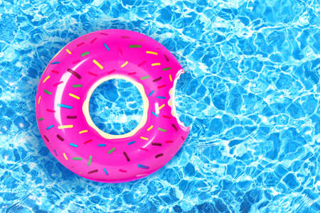 Inflatable colorful donut in swimming pool Banco de Imagens - 90496779