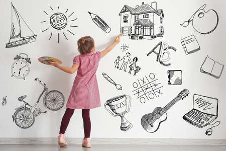Cute little girl drawing on light wall. Different sketches on background