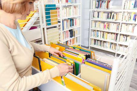Senior librarian working at school library Foto de archivo - 102897860
