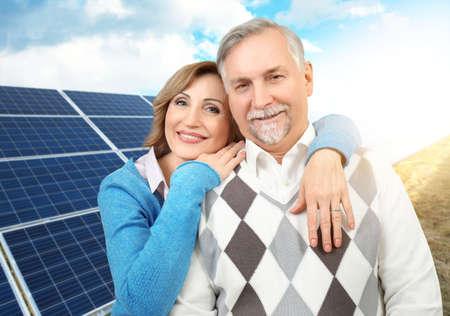 Senior couple and solar panels on background