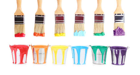 Brushes and buckets with rainbow paints on white background