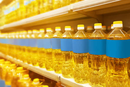 Bottles with cooking oil on shelf in supermarket