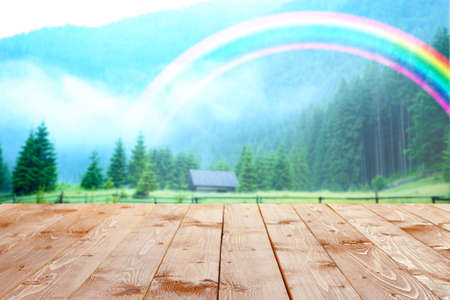 Wooden surface and beautiful landscape with rainbow on background