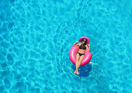 Hermosa mujer joven con donut inflable en piscina