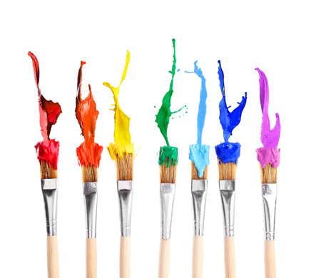Pinceles con salpicaduras de arco iris de pinturas sobre fondo blanco