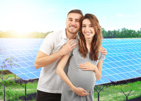Young man with pregnant wife and solar panels on background Stock Photo