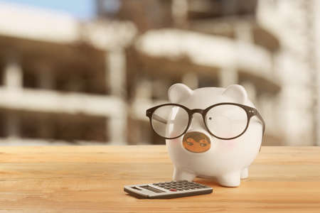 Piggy bank with calculator on table. Mortgage concept Stock Photo