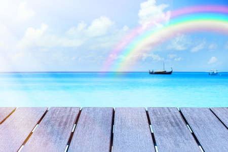 Wooden surface and beautiful seascape with rainbow on background Imagens