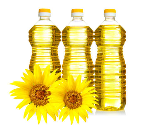 Bottles of cooking oil with sunflowers on white background