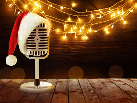 Microphone with Santa hat and garland on background. Christmas music concept