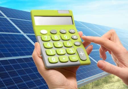 Calculadora da terra arrendada da mulher e painéis solares no fundo. Redução de despesas com eletricidade Foto de archivo