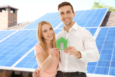 Young couple holding figure of house and solar panels on background