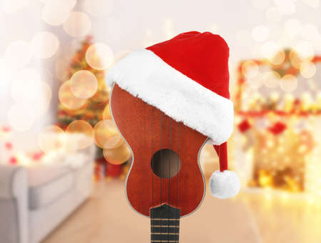 Christmas music concept. Guitar with Santa hat on blurred background Stock Photo