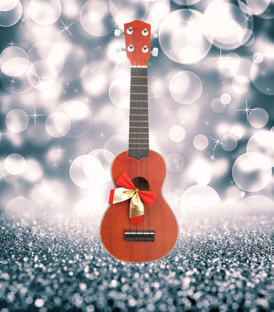 Christmas music concept. Guitar with ribbon bow on blurred background