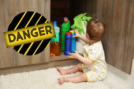 Baby playing with detergents in kitchen Banco de Imagens