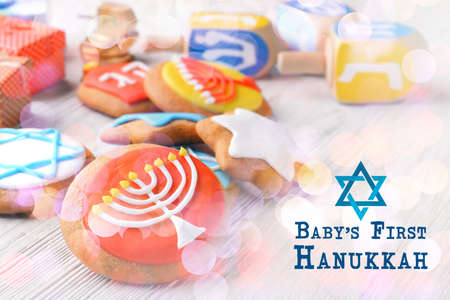 Tasty glazed cookies for babys first Hanukkah on wooden table