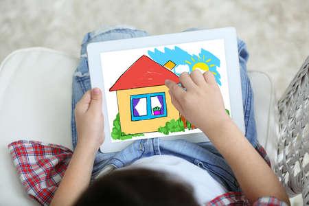 自宅でタブレットに描く小さな男の子 写真素材