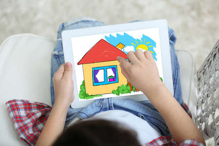 Little boy drawing on tablet at home
