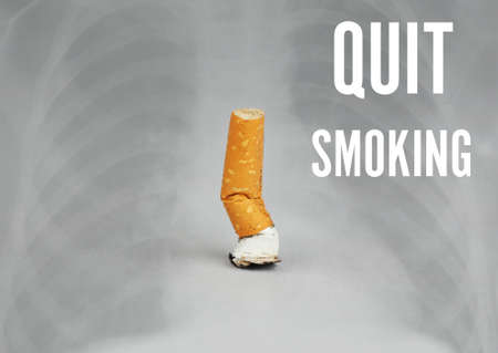 Cigarette butt ant text QUIT SMOKING on light background