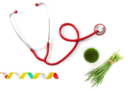Glass of wheat grass juice, measuring tape and stethoscope on white background
