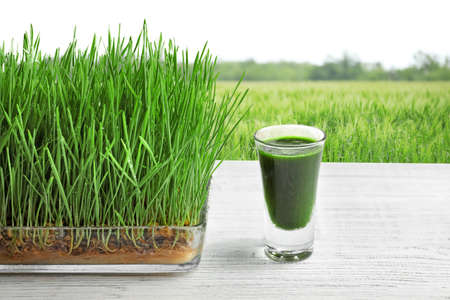 Glass of juice and wheat grass field  on background