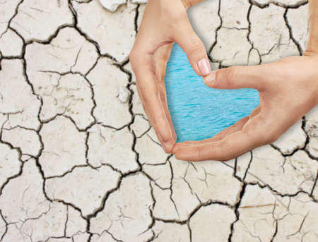 People holding hands in shape of heart and dry soil on background. Concept of water conservation
