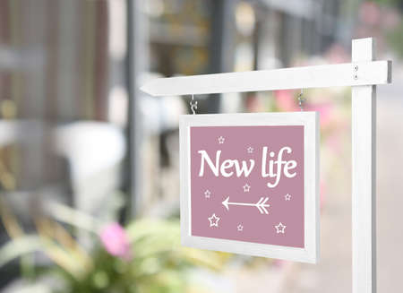 Signboard with text NEW LIFE in front of house