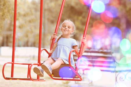 Cute little girl on swing in park Stock Photo - 105290271