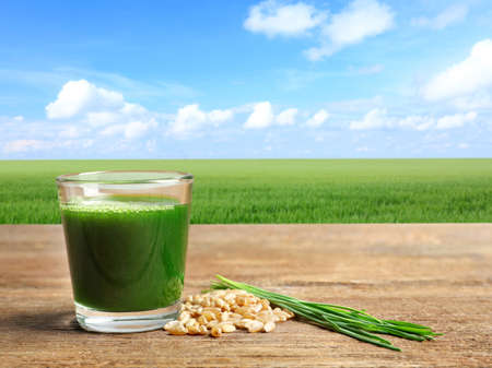 Glass of juice and wheat grass field  on background Stock Photo