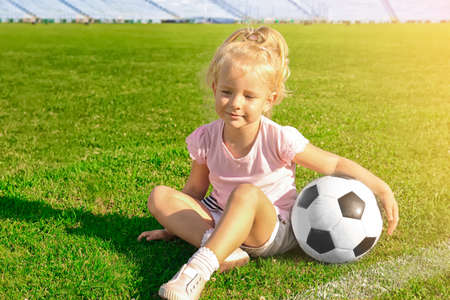Cute girl with soccer ball on field