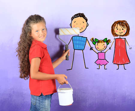 Little girl painting picture on wall Imagens