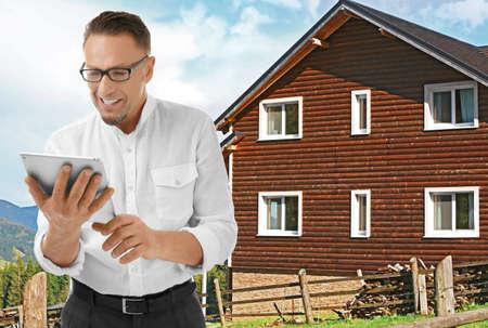 Insurance broker with tablet and building on background Reklamní fotografie