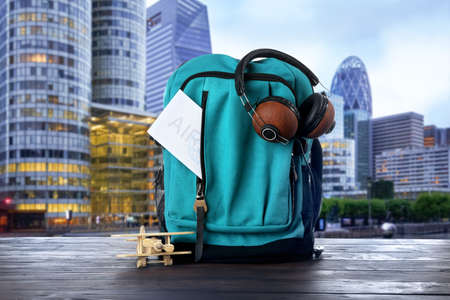 Backpack with headphones and cityscape on background
