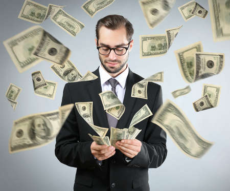 Young man with money on grey background