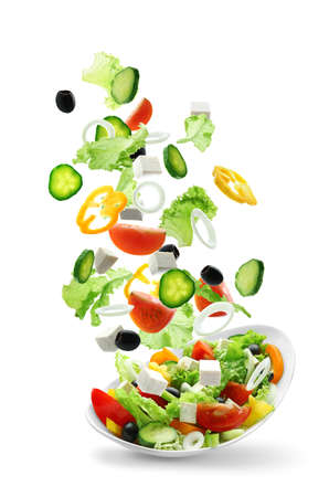 Sliced vegetables falling into bowl with salad on white background