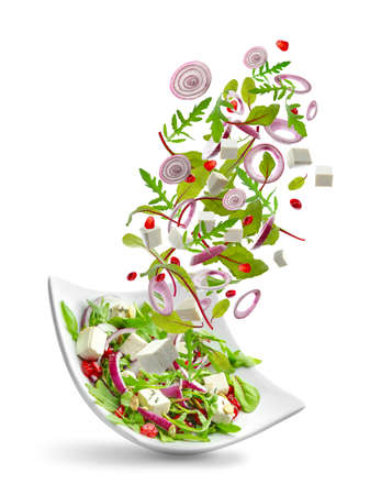 Ingredients falling into bowl with salad on white background
