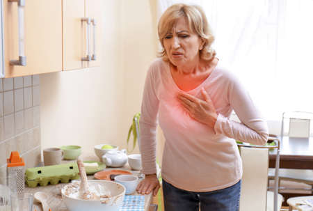 Mature woman suffering from chest pain in kitchen Stock Photo