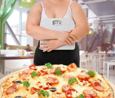 Overweight woman with scales and junk food on blurred background