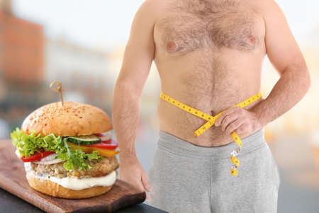 Overweight man with measuring tape and junk food on blurred background