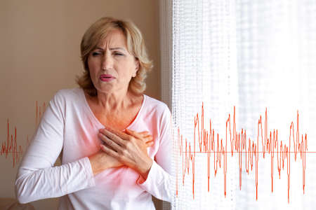Mature woman suffering from heart attack at home 스톡 콘텐츠