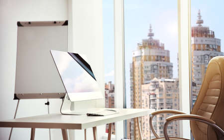 Modern technology concept. Computer on table and cityscape view through window Stock Photo