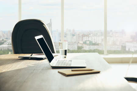 Modern technology concept. Laptop on table and cityscape view through window