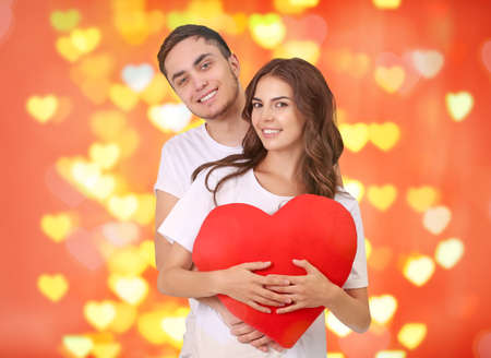 Young couple with heart posing on blurred background