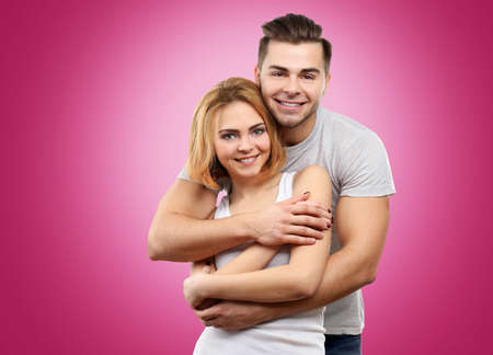 Young couple posing on color background