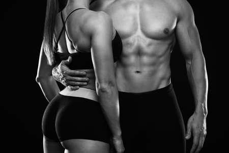 Jovem casal desportivo posando em fundo preto. Foto preto e branco