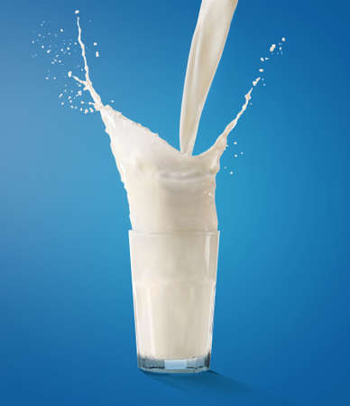 Pouring milk into glass on blue background