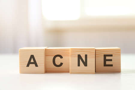 Word ACNE of wooden cubes on table. Skin care concept Stock Photo