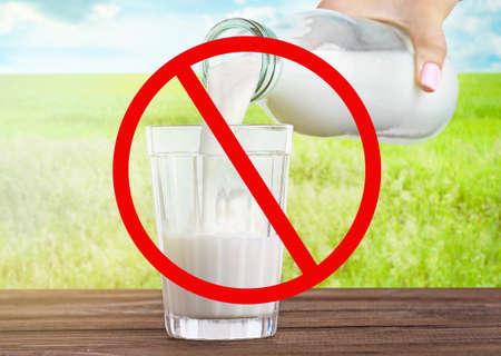 Concetto di prodotti alimentari allergici. La donna che versa il latte dalla bottiglia nel vetro e la restrizione firmano sul fondo della natura Archivio Fotografico - 91102571
